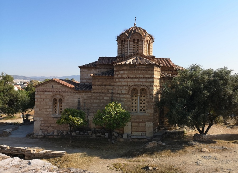A Greek Orthodox Church with towers and dome next to Olive trees