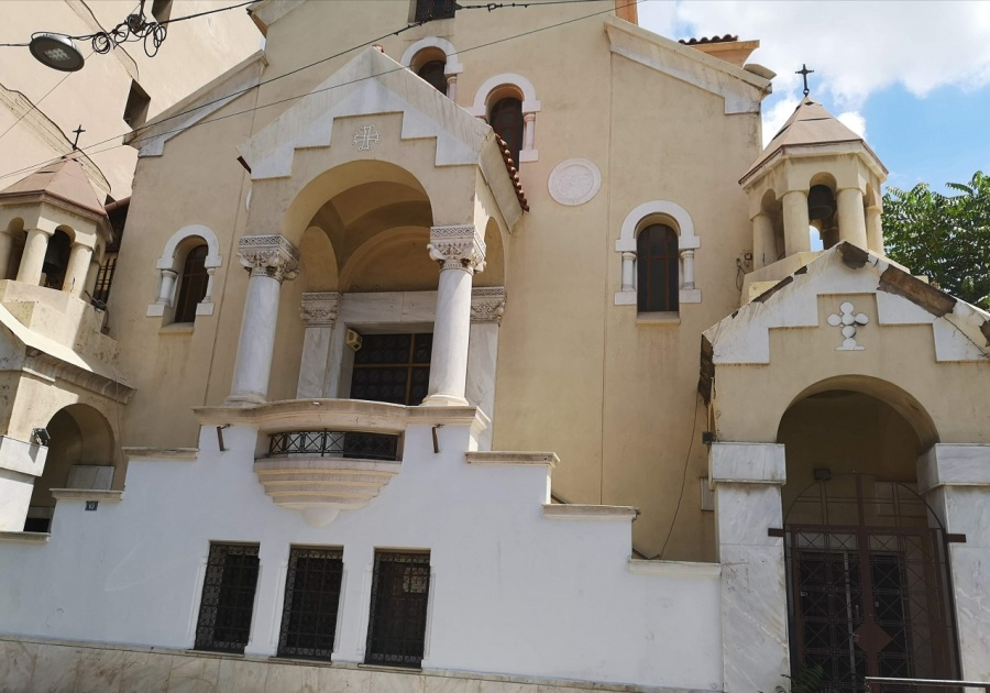 Beige and white Greek Orthodox Church with columns, turrets, crosses and stepped entrance