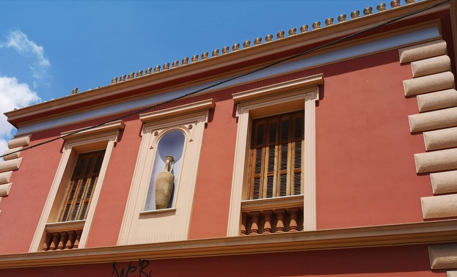 Pink facade with Greek urn, 2 windows and decorated roof