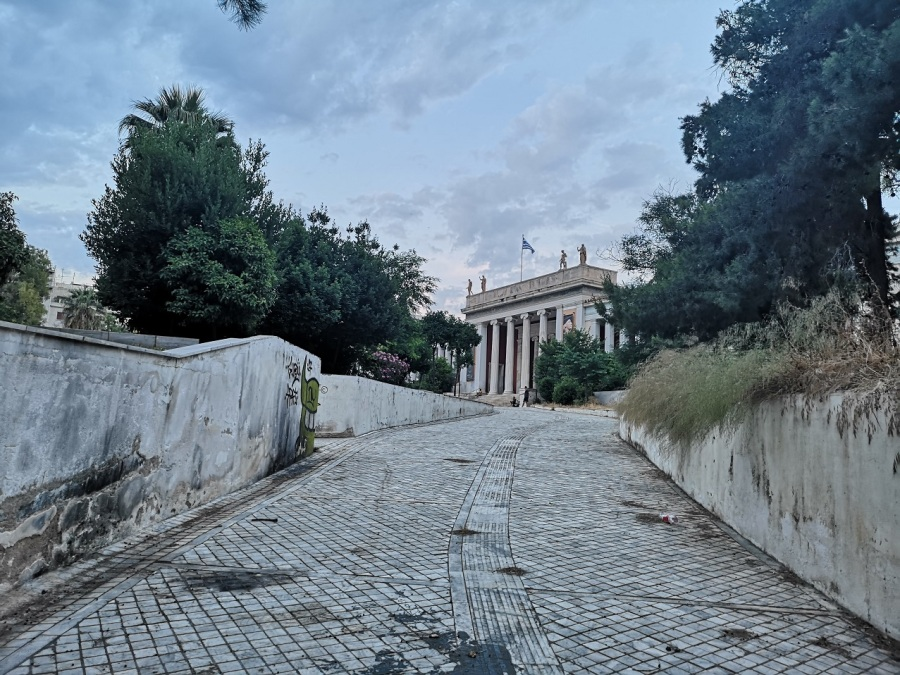 The white Classical architecture of the National Archaeological Museum with trees on either side and the tiled driveway curving up,, Athens, Greece