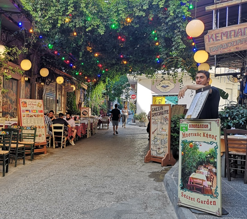 Coloured fairy lights and vines hang above Eschilou street