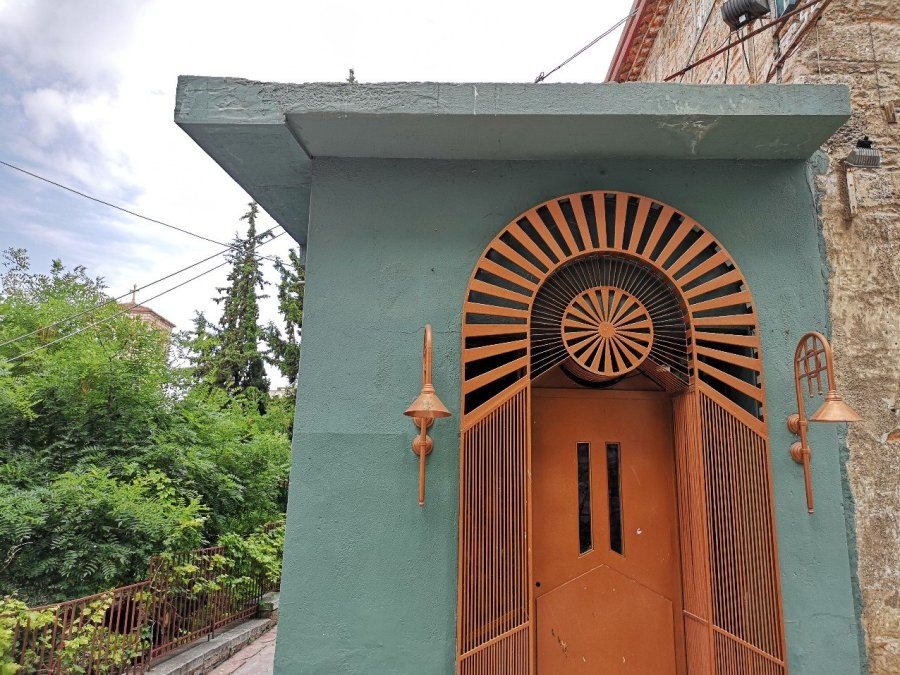 Ornate orange door in a green wall with lamp outside