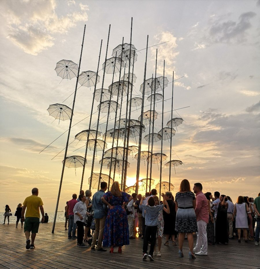 People standing under tall metal umbrellas