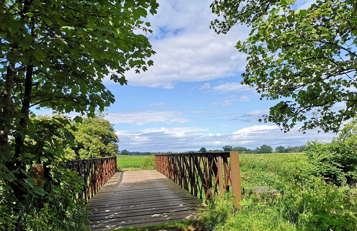 Wooden bridge with red metal railings